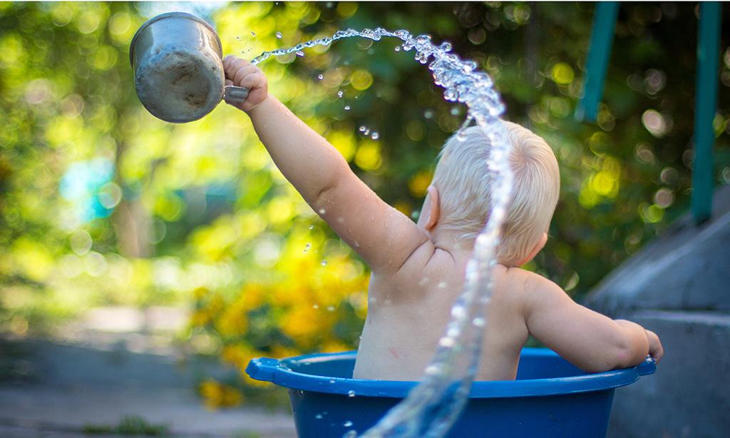bébé s'apergeant avec un gobelet d'eau dans une bassine